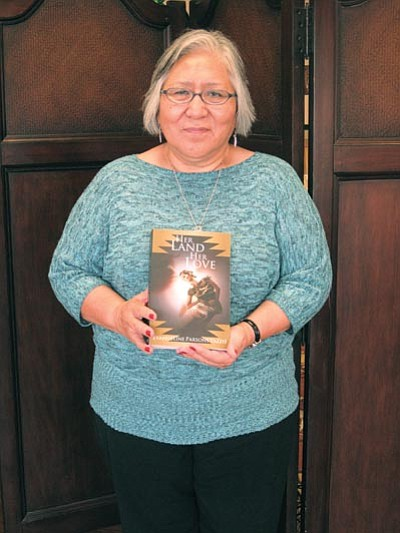 "Local author Evangeline Parsons Yazzie displays her new novel ""Her Land Her Love."" Photo/Loretta Yerian"