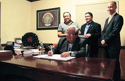 Speaker of the Navajo Nation Council Johnny Naize signs legislation in his office. Photo/Rick Abasta