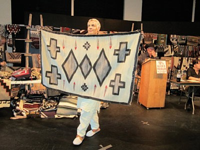 A volunteer displays a rug up for auction during last year's Navajo Rug Auction. Katherine Locke/NHO