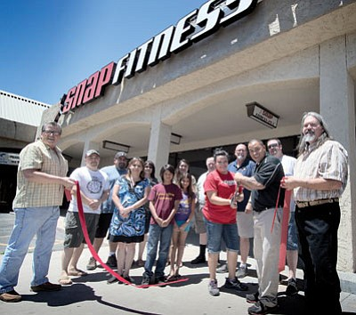 Winslow's Snap Fitness celebrated a ribbon cutting on June 28. Managers Cessie and Michael Lenz  (center, red and black shirts) cut the ribbon. Photo/Todd Roth