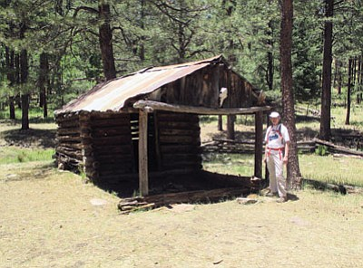 A hiker stands in front of the Pinchot Cabin along the Houston Brothers Trail. Photo/Stan Bindell
