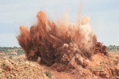 An explosion blows rock apart near U.S. 89. Crews are moving close to a million cubic yards of rock away from the landslide area that closed the road in February. Photo/Arizona Department of Transportation