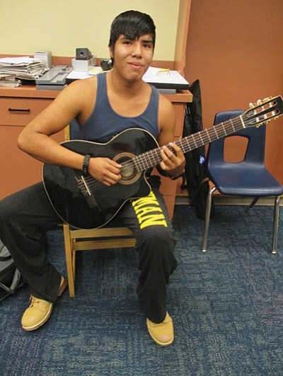 Hopi High School student Star Not Afraid works on his guitar playing. Not Afraid started a music club at Hopi High. Photo/Stan Bindell