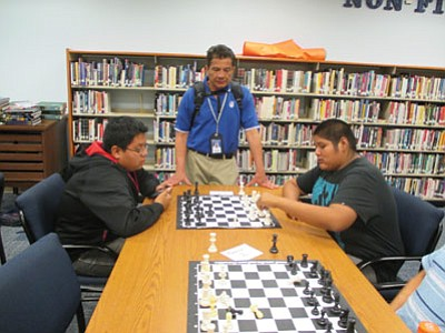 Hopi High chess coach Javier Linarte watches as his players prepare for the Hopi High Invite. Photo/Stan Bindell