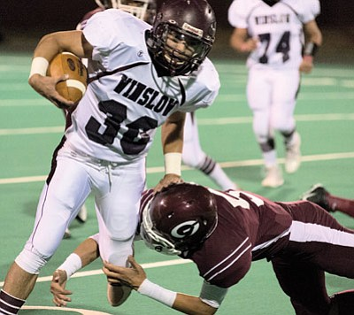 C.J. Chacon breaks a Ganado tackle. The Winslow Bulldogs dominated the Hornets for a 50-3 win Oct. 17. Photo/Todd Roth