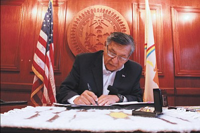 Navajo Nation President Ben Shelly signs the Healthy Dine' Nation Act into law Nov. 20.  The act adds a two percent sales tax to food items with little nutritional value. Photo/Rick Abasta