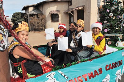 A group of singers from Hotevilla, Kykotsmovi Village and Second Mesa review the lyrics to three carols they planned to sing in Hopi. Photo/Betsey Bruner