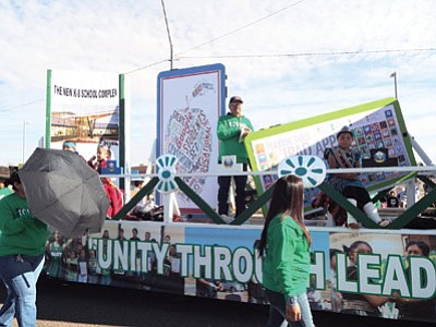 Tuba City Unified School District transportation staff put together a flatbed float to show the technology changes and upgrades that would be possible with with voter approval of a construction bond. The bond passed in the Nov. 4 election. Tuba City School Board member Lee Tsinigine stands at the center of the float during the Western Navajo Nation Fair parade in Tuba City—Moencopi. Photo/Rosanda Suetopka
