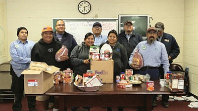 Tuba City Unified School District (TCUSD) Transportation Department employees get ready to distribute turkeys and food boxes with all the holiday trimmings to 10 local families for Thanksgiving.   Pictured from left: Devin Peshlakai, Franklin Williams, Arnold Begay, Heather Williams, TCUSD Transportation Director Orson Bigman, Myrinda Williams, Marvin Nez, TCUSD Head Mechanic Nolan Dempsey and Navajo Hopi Honor Rider Arsenio Brown. Photo/Rosanda Suetopka