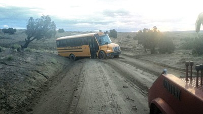 A school bus on Route 16, gets stuck on Inscription House Road on the way to Tuba City. Wet weather has made it difficult for bus drivers to complete their routes to reservation schools without incident. Photo/Rosanda Suetopka