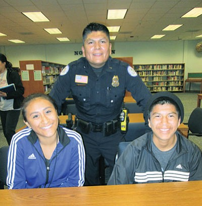 Hopi Police Department Lt. Paul Sidney with Hopi High students Meagan Ua and Christopher Lomayestewa. Photo/Stan Bindell