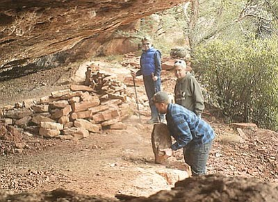 An unidentified man vandalizes Jordan Cave while two people look on. Photo/U.S. Forest service