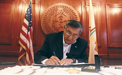 Navajo Nation President Ben Shelly signs legislation March 16 approving a referendum vote on fluency requirements before a general election takes place. Photo/Rick Abasta