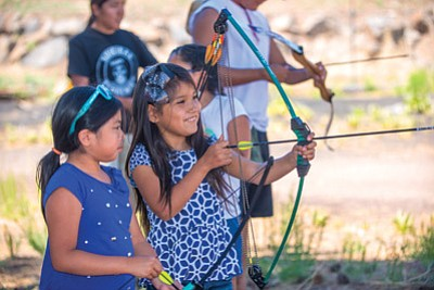 Kids at DinéDiscovery camp learn to shoot a bow and arrow. Photo/Museum of Northern Arizona
