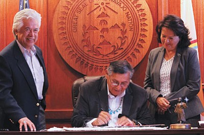Navajo Nation President Ben Shelly signs a cooperative agreement for the Buy-Back Program. Photo/Rick Abasta