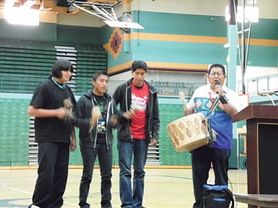 Clark Tenakhongva, Hopi tribal member and Canyon Records performing artist, sings a Hopi social dance song with Tuba City High School students Tyler Scott, Kyle Sumatzkuku and Paul Rogers during a performance in Tuba City High School's Warrior Pavilion. Photo/Rosanda Suetopka