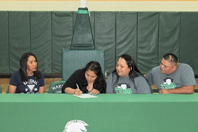 Tuba City High School senior Samytha Parrish signs a full ride scholarship to Chandler GIlbert Community College to play both basketball and volleyball while earning a degree in biology. Parrish is flanked by her coach Kim Williams (left) and her parents, Gwenytha and Sam Parrish of Tuba City. Photo/Rosanda Suetopka