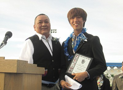 Co-Valedictorian Jason Lim receives a plaque from Hopi Jr./Sr. High School Governing Board member Marvin Yoyokie. Photo/Stan Bindell