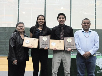 Tate Tsingine and Christian Begody, Tuba City High seniors, took both categories of Athletes of the Year 2015 and also Student Academic Athletes of the Year 2015 at the recent sports banquet at Tuba City High Warrior Pavilion. From left: Tuba City Unifieid School District Governing Board member Mary Worker, Tate Tsingine, Christian Begody and Board President William Longreed.  Photo/Rosanda Suetopka