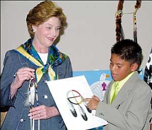 Photo by Debra Utacia Krol  Preston Doctor, 11 explains the elements of the medicine wheel to First Lady Laura Bush.