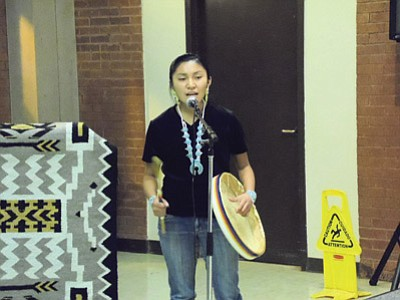 Tuba City High School student Mia Keeswood performs a song she wrote using a hand drum as accompaniment. She takes her Navajo language seriously enough to use in it her own creative process. Keeswood is an example of learning