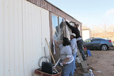 People seal air leaks after a recent Red Feather weatherization workshop. Photo/Joe Seidenberg