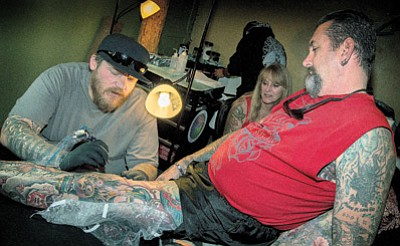 A tattoo artist from Flagstaff's Black Bart Tattoo works on a customer during Inkfest at PT's Bar in Winslow Oct. 24. Todd Roth/NHO