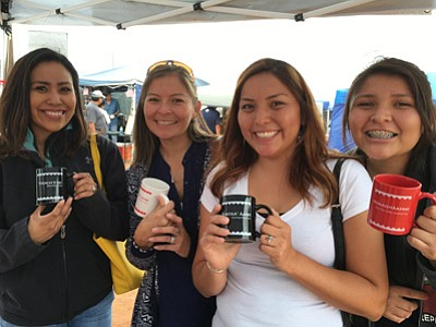 Several attendees at October's Tuba City Fair hold up coffee mugs with Navajo clan names. Submitted photo