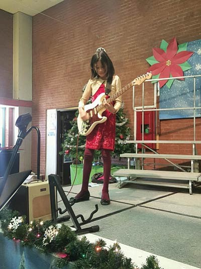 Kara Allen, a fifth grade student at Tuba City Primary shows her guitar prowess with a solo electric guitar performance in the cafeteria. Rosanda Suetopka/NHO