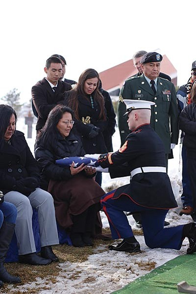 A member of the United States Marine Corps Honor Guard presents the flag to the daughter of Navajo Code Talker Ernest Yazhe. Submitted photo