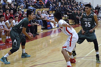 Tuba City Warriors Roland Becenti (13) looks to drive around a Holbrook defender while Warrior's Urijah Yazzie (35) sets a pick during basketball action at Munoz Gym in Holbrook, Arizona.  Holbrook defeated Tuba City, 53-42 Jan. 19.  Photo/Anton Wero