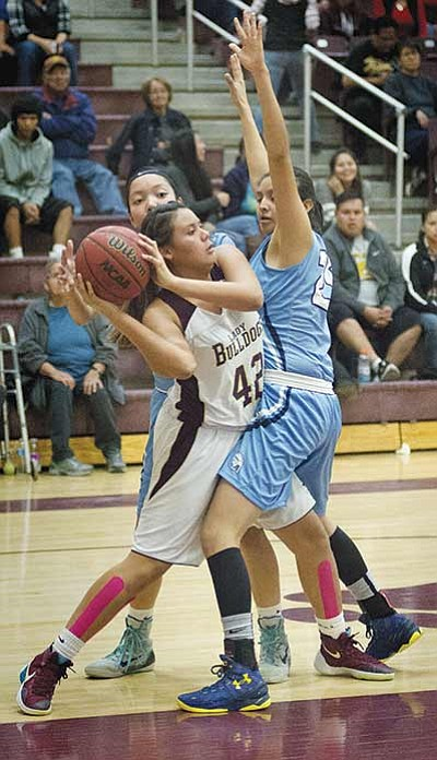 Winslow Bulldogs Justine Butterfield works around two Window Rock Scouts defenders. Winslow prevailed 58-43 Jan. 29.  Photo/Todd Roth