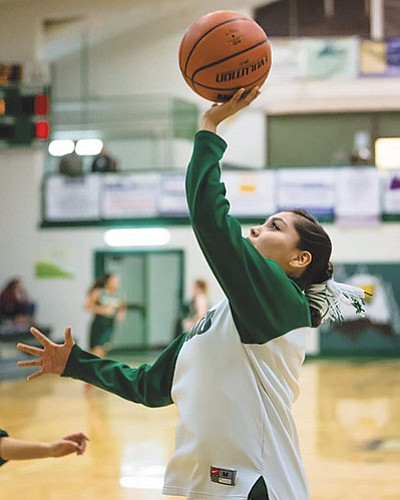 A Navajo Flagstaff High School Lady Eagles basketball player warms up before a Feb. 2 game with her hair in a tsiiyeeł, a traditional Navajo hairstyle. Photo/Rick Johnson Photography