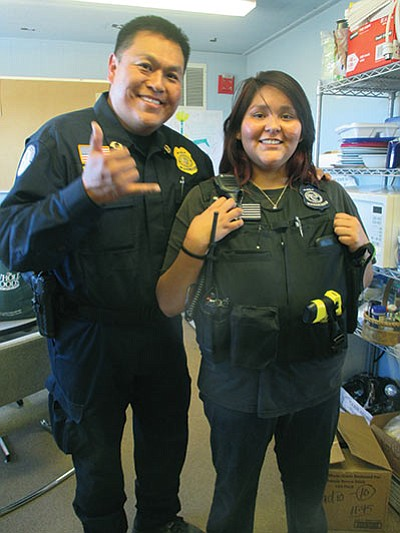 Hopi High radio student Reyna Lomayaktewa tries on a police vest with Police Chief Jamie Kootswatewa. Stan Bindell/NHO