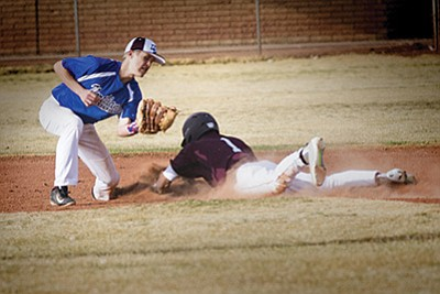 A Bulldogs base runner beats the tag at second base on the way to a 10-0 win against Northland Prep March 7. Photo/Todd Roth