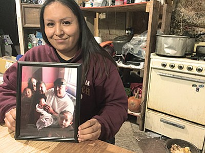 LaTanya Dickson holds a picture in her kitchen of her family, which includes a picture of her daughter Lisa, who cannot return home until the family's house has running water and electricity. Submitted photo