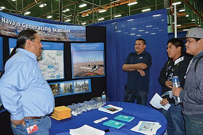 Navajo Generating Station representatives Franco Begay and Kolton Chato talk to Tuba City High School students about electrical engineering during a recent Career Fair. Photo/Tia Folgherator