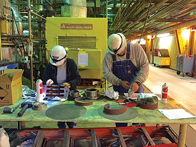 Navajo Generating Station Plant Mechanic Journeyman Tashina Tsinnijinnie (left) and Plant Mechanic Apprentice Christopher Chischilly clean bearing housings prior to reassembly of the Charlie Boiler Feed Booster Pump. Photo/George Hardeen