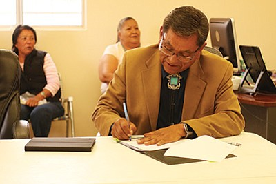Navajo Nation President Russell Begaye signs off on a budget for the Coppermine Chapter to begin building and renovating houses.  Submitted photo