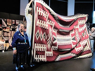 Volunteers attempt to hold up Bessie Yazzie's 12-foot-9–inch by 9-foot-9-inch rug in preparation for the auction in 2013. Katherine Locke/NHO
