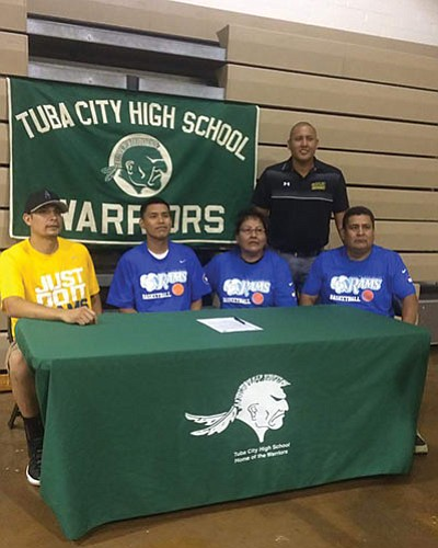 Davean Yazzie, from Tuba City High School, signs a letter of intent to play basketball at Little Bighorn Horn College in Montana. From left: coach Wes Spotted Bear, Davean Yazzie, his mother Denise Becenti and father William Yazzie. Submitted photo