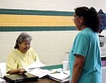 Rosanda Suetopka Thayer/TC District Media  Delores Hyden (left), staff member of the Tuba City High School library assists parents at the Warrior Pavilion with early registration that started this week at Tuba City District #15.