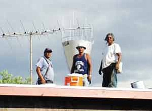 "Photo by Rosanda Suetopka Thayer <BR><BR> This past week, the ""Hotevilla Roofers""—Wilfred Kaye, left, Edgar Rogers and Gale Albert, put in overtime in the extreme heat and high winds on their mesa top to tear off old roofing materials to replace with new watertight roofs for their honored and eldest tribal members."