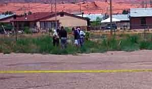 Photo by James Nez  Far right, Clarence Elliot, NNCI Evidence Tech., along with federal agents make cast moldings of foot prints near the crime scene by Kayenta DraperÕs Glass Company.
