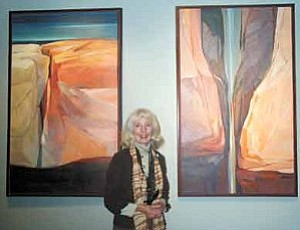 "Ann Widmann/Observer<BR><BR> Joella Jean Mahoney poses between two of her pieces ""Kayenta  Canyon,"" left, and ""Inner Gorge."""