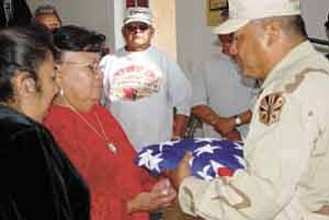Photo by Rosanda Suetopka Thayer   Army widow, Marlene Rosetta, accepts a flag for her husband, Johnny Rosetta's service to this country. Rosetta's daughter was also in attendance to accept the flag on behalf of her father.