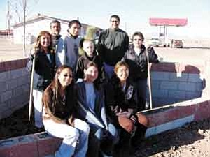 S.J. Wilson/Observer<BR><BR> Afton Solomon, Keshia Yazzie, Monique Reveles (front), Pricilla Half, Justin Willie, Kevin Begay, Miles Sorenson, Thomas Cody and Clara Tsosie admire the masonry work of Furdale Smith, a local resident. The young people, students of the STAR School, volunteered to spread decorative gravel and place stones on Nov. 30.