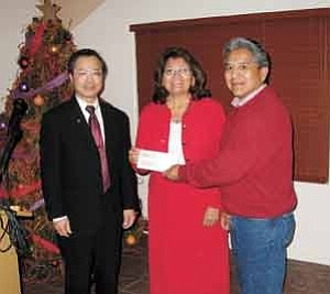 Photo by George Hardeen Pacific Western Technologies CEO Tai-Dan Hsu, left, presents a check for $10,000 to Boys & Girls Club of the DinZ<caron> Nation director Marilyn King-Johnson and Division of DinZ<caron> Education executive director Leland Leonard at a dinner on Dec. 17.