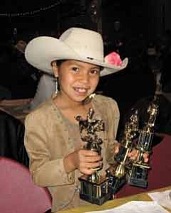 Photo by George Hardeen  Kylie Yazzie holds three of her trophies won at the Indian Junior Rodeo Association Awards Banquet at Red Rock State Park on Saturday. Kylie also sang the National Anthem at the opening of the banquet.