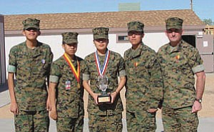 Members of the award-winning team are (l-r) Darrell Robbins – fourth place Marine Corps, 17th overall; Darrin Talawepi – eighth place Marine Corps, 35th overall; Ashley Manygoats – Marine Corps Individual National Champion, 10th place overall, and  Charles Lee – second place Marine Corps, 12th place overall, with their coach, Gunnery Sgt. Tim Shaner.